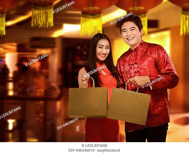 Asian couple in cheongsam suit with shopping bag. Happy chinese new year concept