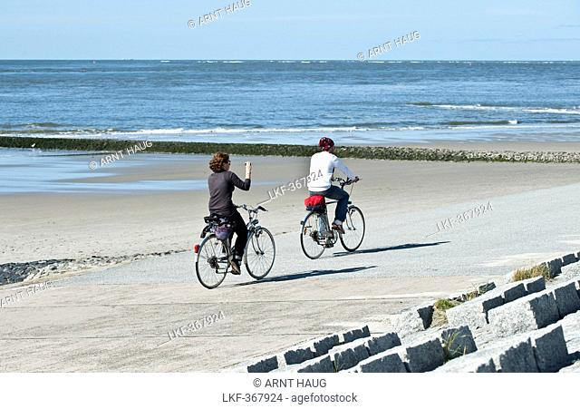Two cyclists passing promenade, Norderney, East Frisian Islands, Lower Saxony, Germany