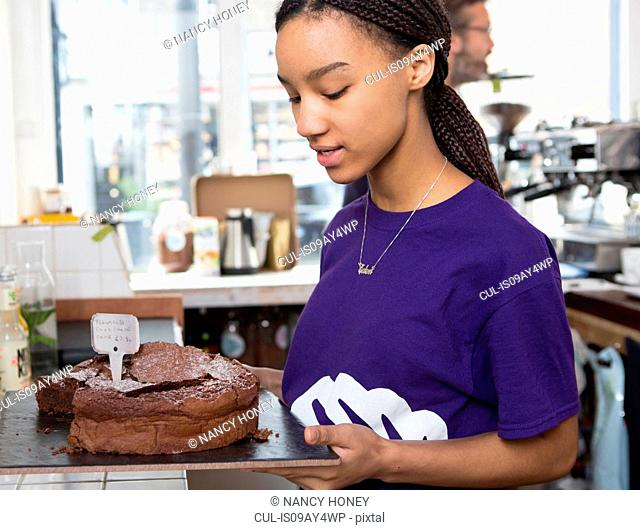 Waitress removing chocolate cake from cafe counter