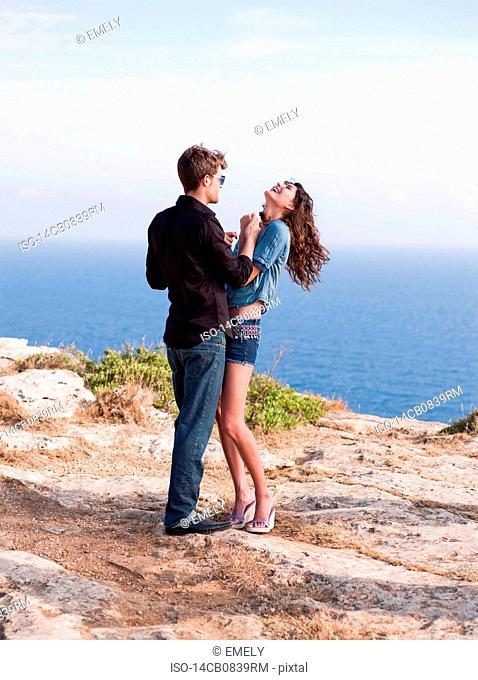 couple standing at cliff holding hands