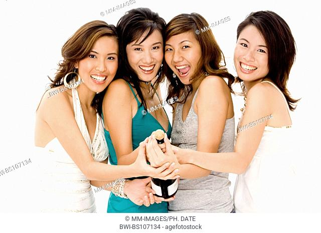Four pretty young Asian women opening a bottle of champagne