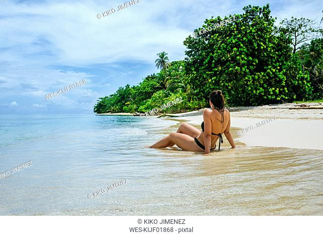 Panama, Bocas del Toro, Cayo Zapatilla, Woman sitting on the beach