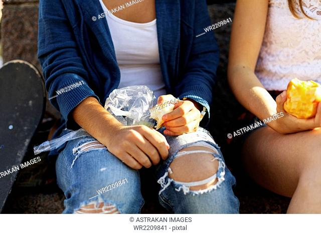 Close-up of girls eating apple while sitting on retaining wall