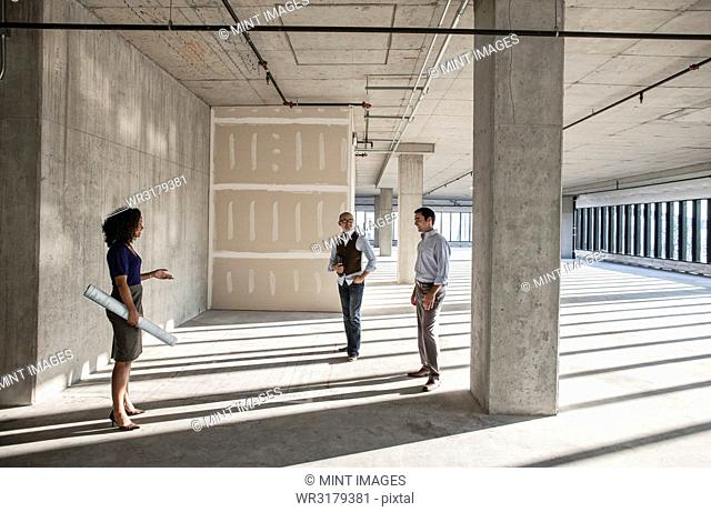 Mixed race team of business people touring a new empty raw office space