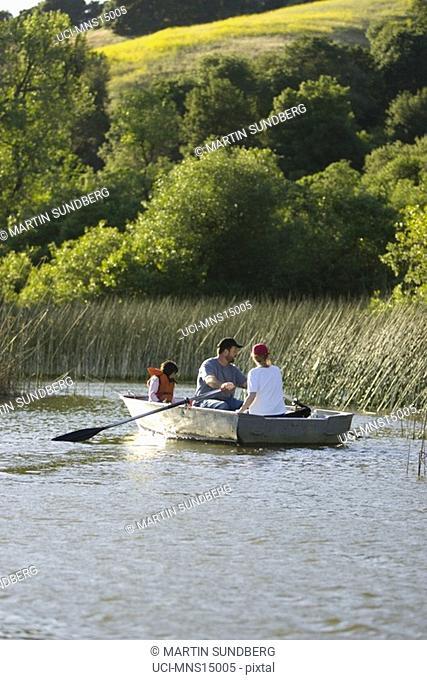 Family fishing in boat on lake in California