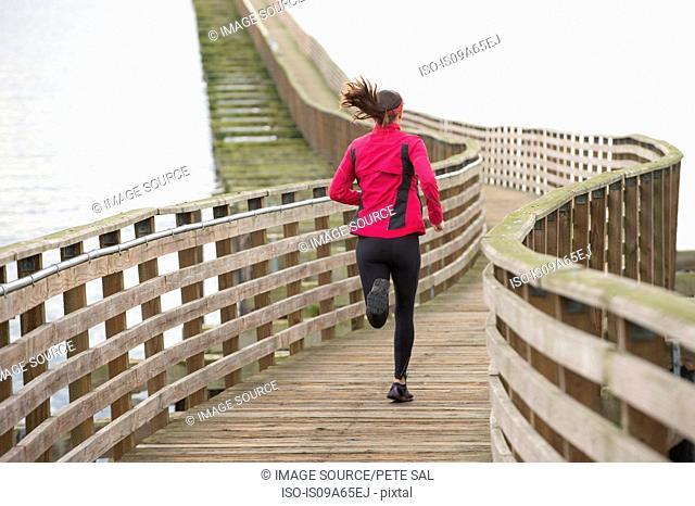 Woman running on wooden dock