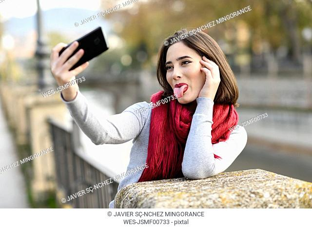 Portrait of young woman wearing red scarf sticking out tongue taking selfie with cell phone