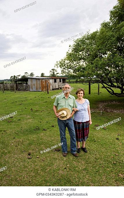 Senior couple standing in field of rural home