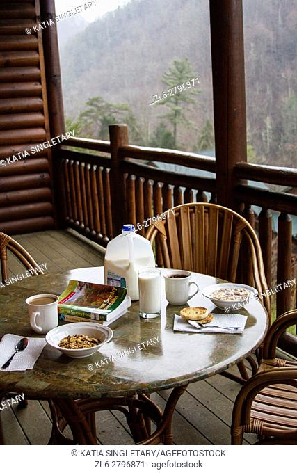 Breakfast table set with milk and cereals on the wooded balcony of a ski resort. The view from the mountains is incredible