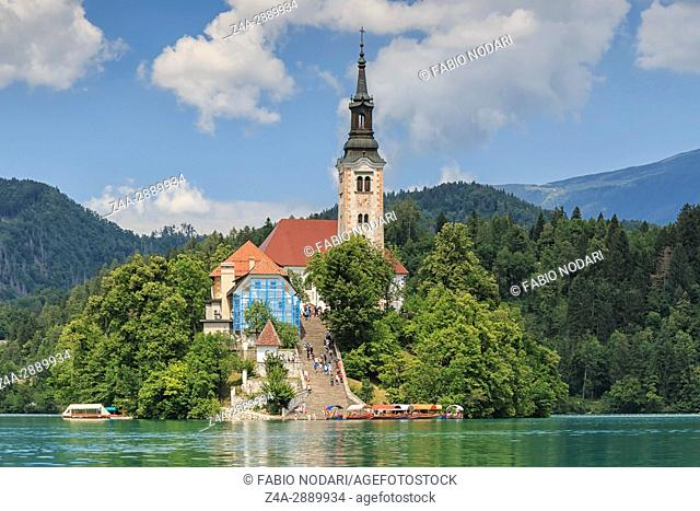 Close up of the church in the center of Bled Lake with several tourists walking by
