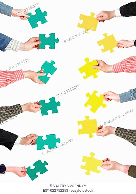 green and yellow puzzle pieces in people hands