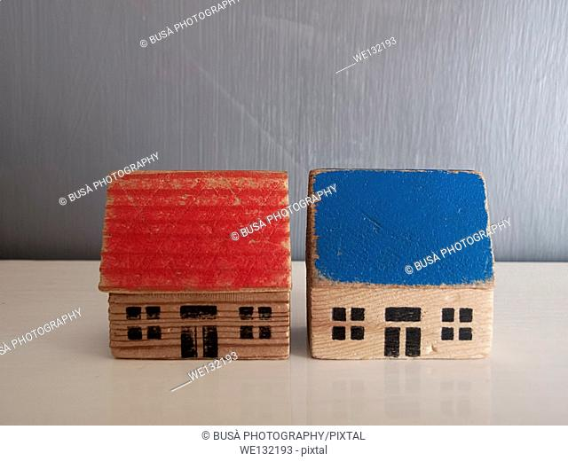 Two miniature houses on a grey background