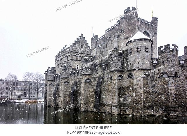 Medieval Gravensteen / castle of the counts in the historic city centre of Ghent during snow shower in winter, East Flanders, Belgium