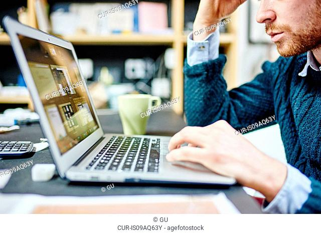 Cropped shot of man typing on laptop at desk in traditional workshop