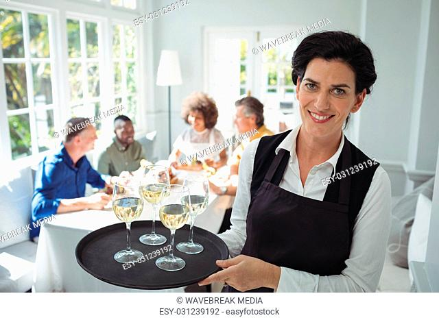 Smiling waitress holding glasses of wine in tray