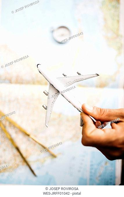 Hand holding airplane model in front of world map