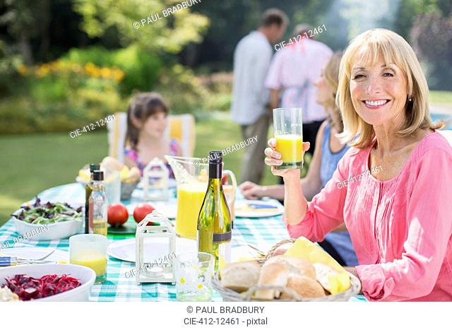 Smiling woman enjoying lunch at table in backyard