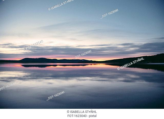 Idyllic view of lake and mountains in silhouette against dramatic sky at sunset