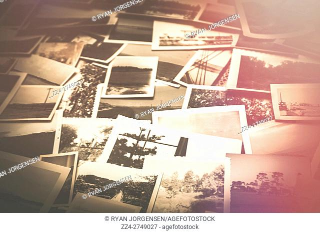 Pile of old scattered photos background with red light leak fade. In memory of nostalgia