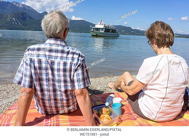 senior couple relaxing at lakeside and watching ship during vacations at lake in Bavaria, Germany