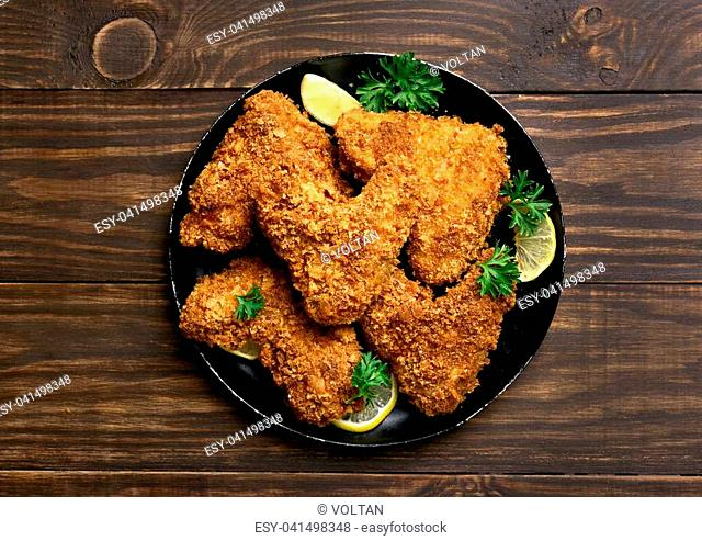 Fried breaded chicken wings on plate over wooden background. Top view, flat lay food