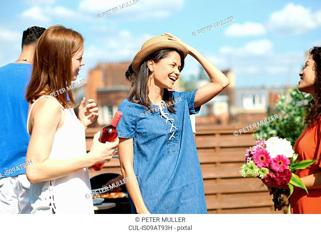 Female friends chatting and laughing at rooftop party