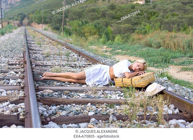 Young woman sleeping on railroad track