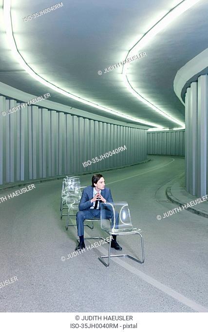 Businessman in chairs in empty hallway