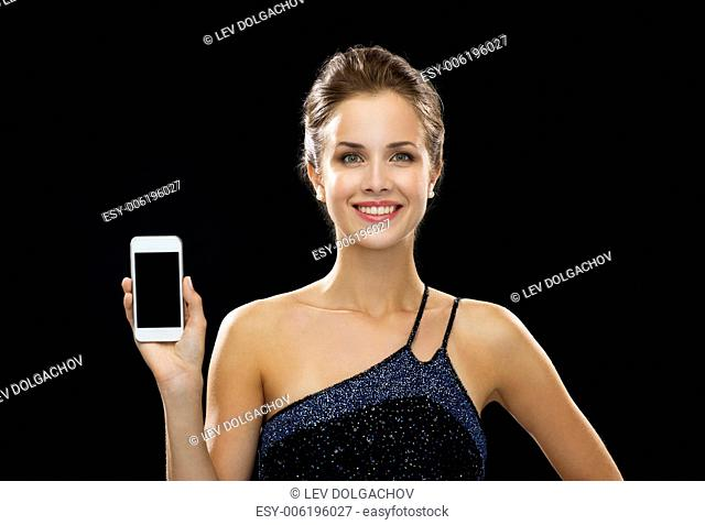 technology, advertisement and lifestyle concept - smiling woman in evening dress with blank smartphone screen over black background