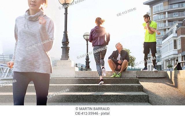 Runners resting, stretching and running on sunny urban steps
