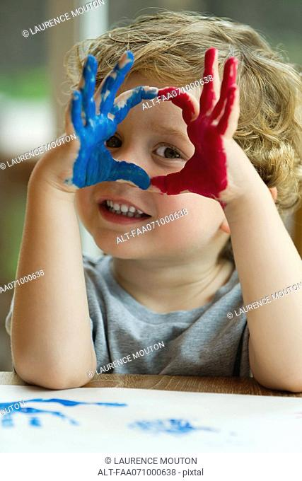 Little boy with hands covered in paint
