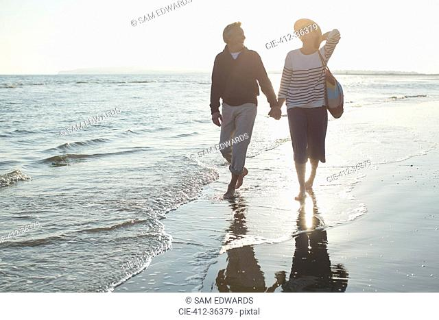 Affectionate mature couple holding hands and walking on sunset ocean beach surf