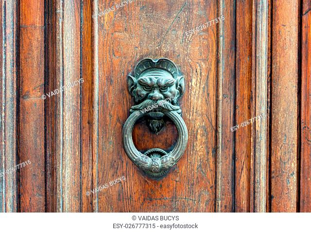 Iron lion doorknob on the old weathered wooden door in Florence, Italy