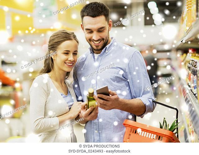 couple with smartphone buying olive oil at grocery