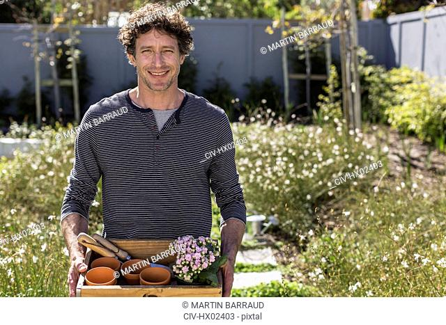 Portrait smiling man holding gardening tray in sunny garden