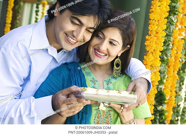 Young couple holding a tray of cookies