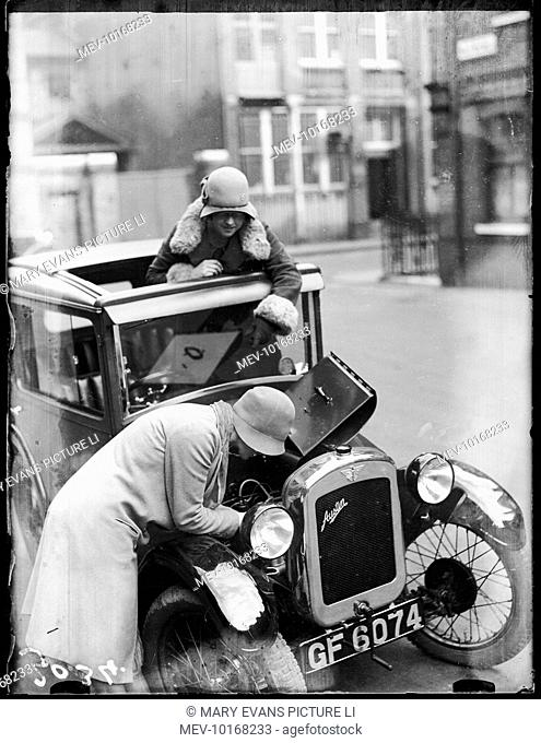Two fashionable young ladies in cloche hats, one of them with the car bonnet open, trying to work out how to mend the engine!