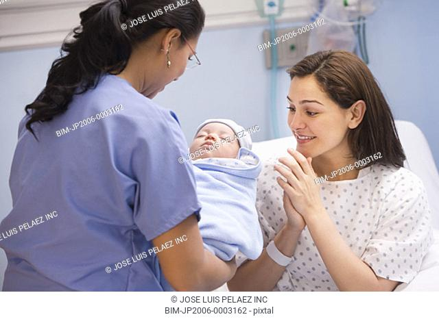 Female nurse handing newborn baby to mother