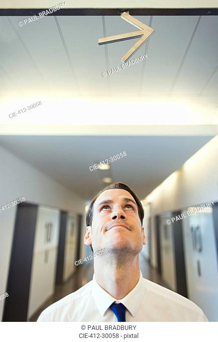 Businessman looking up at arrow overhead