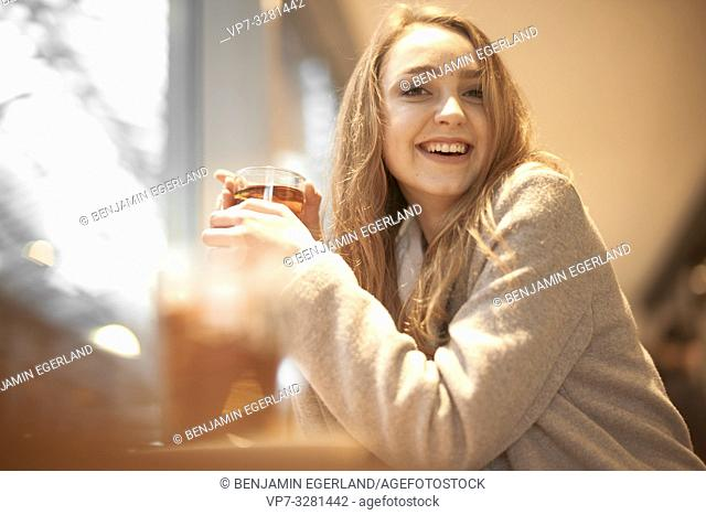 young woman with warm tea in hands, indoors in café, in Cottbus, Brandenburg, Germany