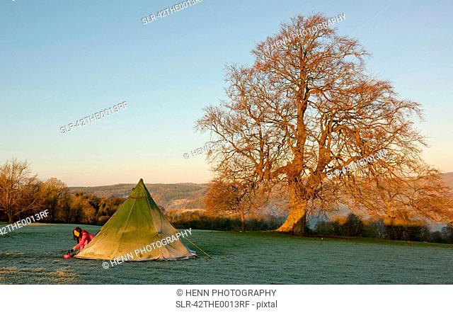 Girl climbing out of tent at campsite