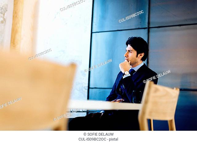 Businessman sitting at desk, thoughtful expression