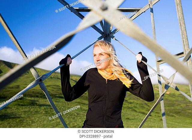 A Young Woman Stands Holding The Metal Bars Of A Transmission Tower; False Pass, Alaska, United States Of America