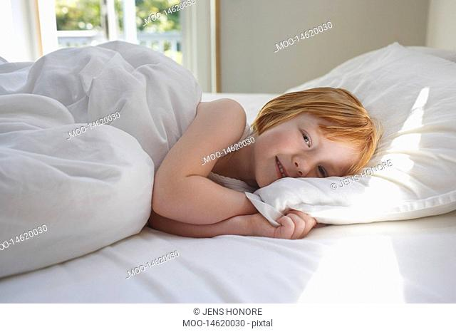 Portrait of girl 5-6 lying in bed smiling