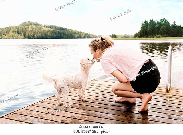 Woman kissing coton de tulear dog on pier, Orivesi, Finland