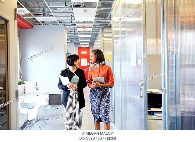 Two businesswomen walking along office corridor, in conversation