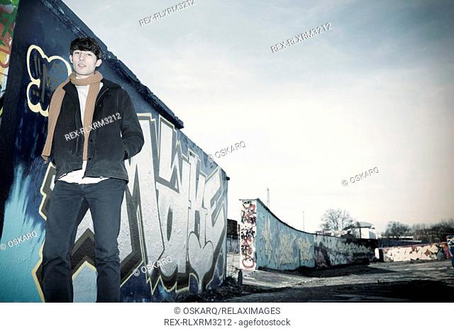 Young man leaning against wall outdoors graffiti