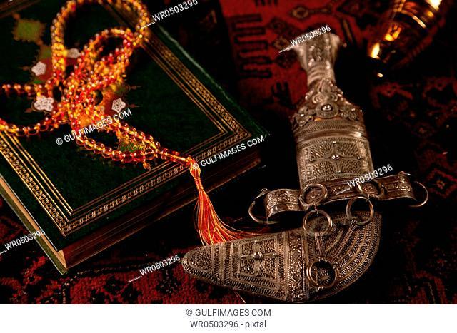 Prayer beads on top of a Quran with a khanjar