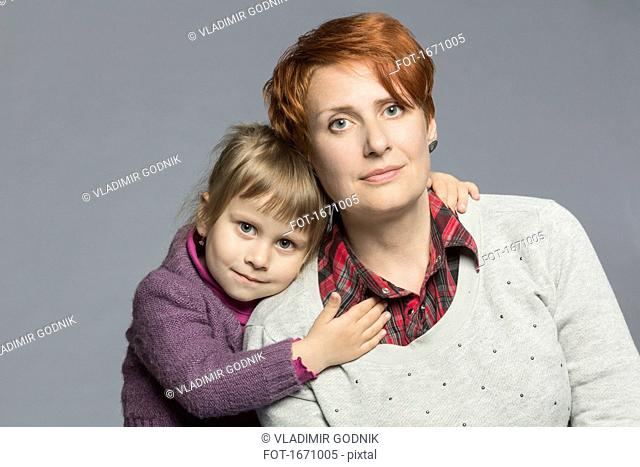 Portrait of daughter embracing mother against gray background