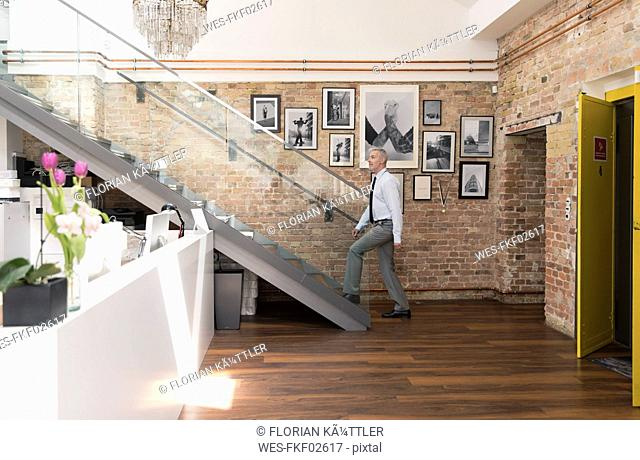 Mature businessman in modern office ascending stairs